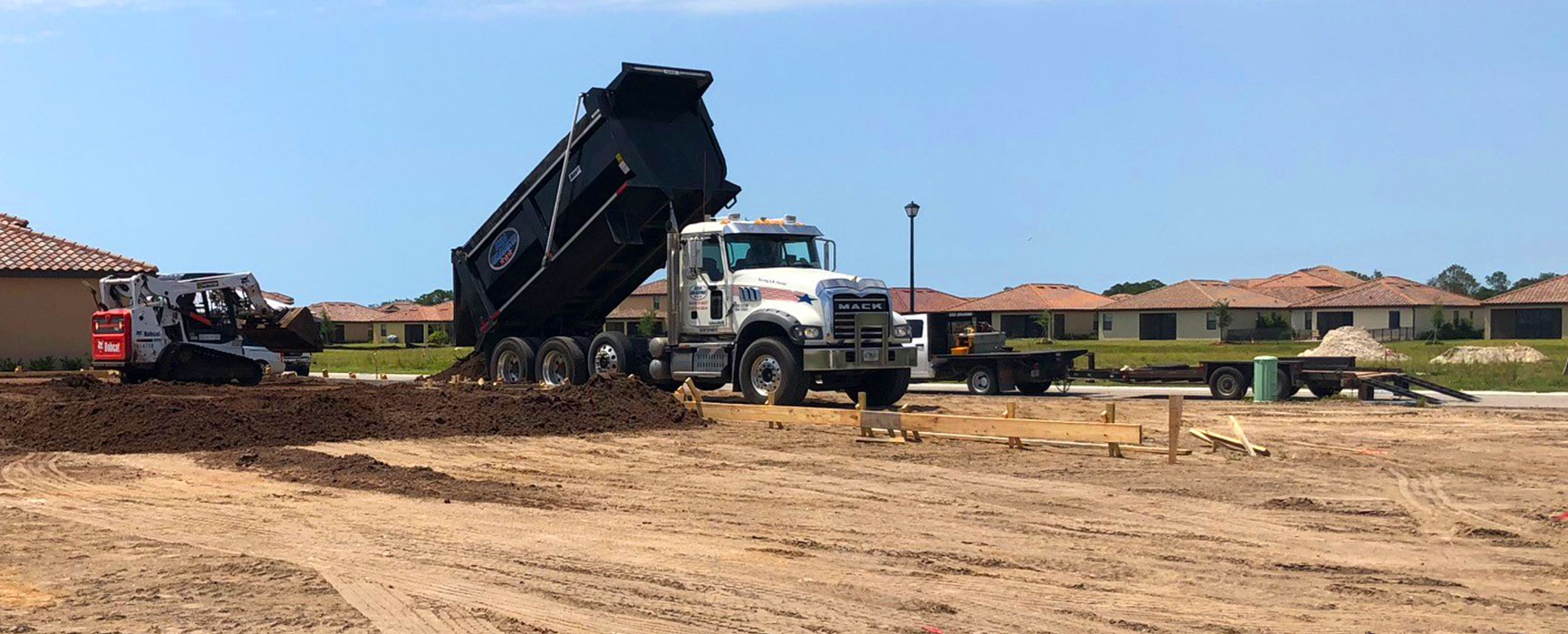 USA Grading, Inc. truck unloading fill dirt and performing site grading in a Southwest Florida residential area