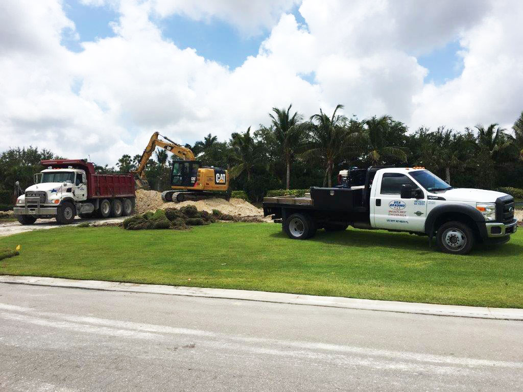 USA Grading, Inc. truck, bulldozer and large haul truck with a pile of residential fill dirt in Southwest Florida
